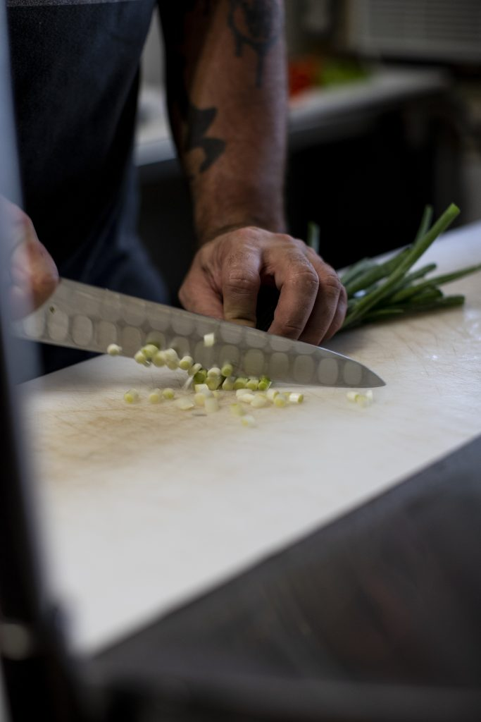 Chef Jessie Steele chopping scallions at Dada in Delray Beach