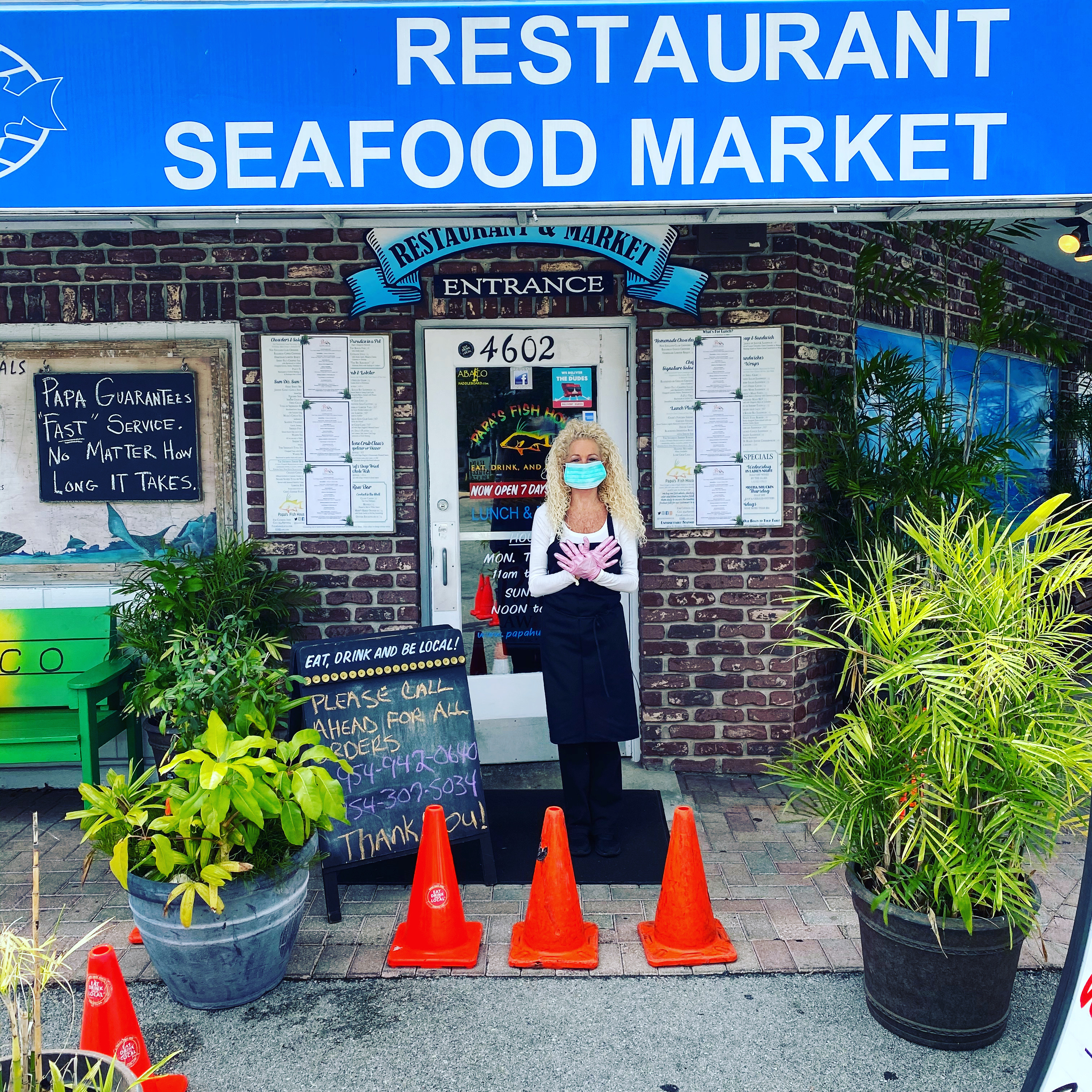 Employee in mask and gloves in front of Seafood World